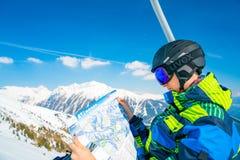 Homem novo que monta acima do elevador de esqui que explora o mapa da estância de esqui Fotos de Stock Royalty Free