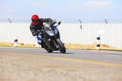 Homem novo que monta a motocicleta grande da bicicleta na estrada asfaltada afiada da curva Fotografia de Stock Royalty Free