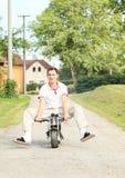 Homem novo que monta o velomotor pequeno Foto de Stock