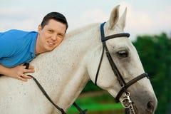 Homem novo que monta um cavalo no por do sol na praia Homem com hors Fotografia de Stock Royalty Free