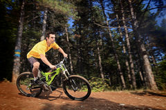 Homem novo que monta um estilo em declive da bicicleta de montanha Fotografia de Stock Royalty Free