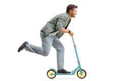 Homem novo que monta um 'trotinette' Fotografia de Stock