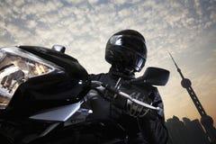 Homem novo que monta uma motocicleta durante o dia, céu e construindo exteriores no fundo Fotografia de Stock Royalty Free