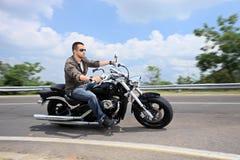 Homem novo que monta uma motocicleta em uma estrada aberta Fotos de Stock