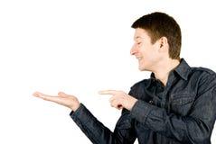 Homem novo que mostra algo em sua mão Fotos de Stock Royalty Free