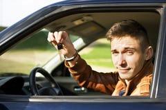 Homem novo que mostra chaves do carro - imagem conservada em estoque Imagens de Stock