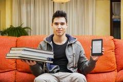 Homem novo que mostra a diferença entre o leitor do ebook e livros pesados Fotografia de Stock