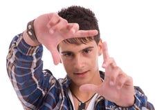 Homem novo que mostra o gesto de mão de quadro Fotos de Stock Royalty Free