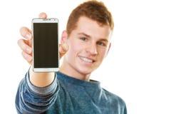 Homem novo que mostra a tela vazia preta do telefone Imagem de Stock