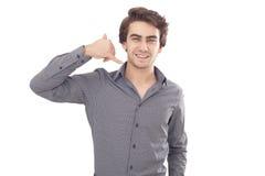 Homem novo que mostra um gesto do telefonema Fotografia de Stock