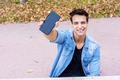 Homem novo que mostra uma tela preta vazia de seu telefone celular em t fotografia de stock
