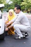 Homem novo que muda o pneumático puncionado fotos de stock