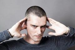 Homem novo que obstrui as orelhas para evitar escutar problemas Fotos de Stock