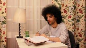 homem novo que obtém sonolento ao estudar vídeos de arquivo