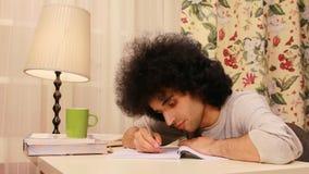 homem novo que obtém sonolento ao estudar 2 vídeos de arquivo