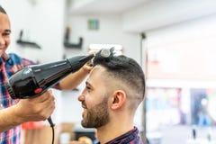 Homem novo que obtém um penteado em um barbeiro foto de stock
