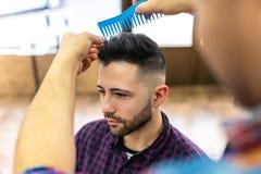 Homem novo que obtém um penteado em um barbeiro imagens de stock royalty free