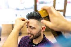 Homem novo que obtém um penteado em um barbeiro fotos de stock royalty free