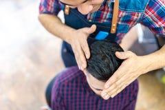 Homem novo que obtém um penteado em um barbeiro foto de stock royalty free