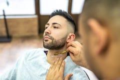 Homem novo que obtém uma barba barbeada foto de stock royalty free