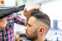 Homem novo que obt?m um penteado em um barbeiro imagens de stock