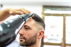 Homem novo que obt?m um penteado em um barbeiro imagem de stock royalty free