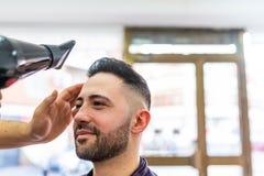 Homem novo que obt?m um penteado em um barbeiro fotografia de stock