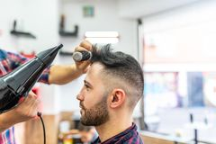 Homem novo que obt?m um penteado em um barbeiro foto de stock royalty free