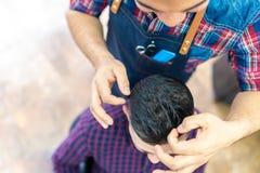 Homem novo que obt?m um penteado em um barbeiro fotografia de stock royalty free