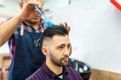 Homem novo que obt?m um penteado em um barbeiro imagens de stock royalty free