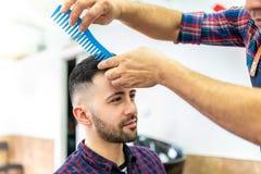 Homem novo que obt?m um penteado em um barbeiro fotos de stock