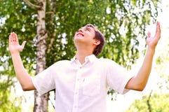 Homem novo que olha ao céu, mantendo suas mãos Fotografia de Stock