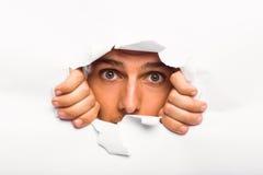 Homem novo que olha através do rasgo de papel Imagens de Stock Royalty Free