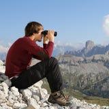 Homem novo que olha através dos binóculos nas montanhas Fotografia de Stock Royalty Free