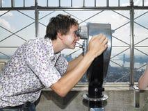 Homem novo que olha através do telescópio Fotos de Stock