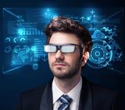Homem novo que olha com elevação esperta futurista - vidros da tecnologia Fotografia de Stock Royalty Free