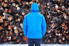 Homem novo que olha fixamente na pilha do log Imagens de Stock