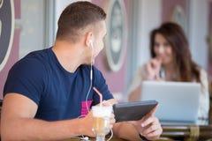 Homem novo que olha a menina em um café Imagem de Stock