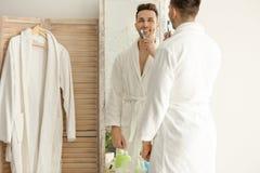 Homem novo que olha no espelho ao escovar os dentes foto de stock