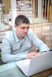 Homem novo que olha no portátil Imagem de Stock