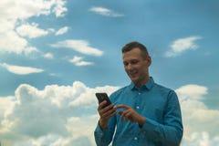 Homem novo que olha o gesto do telefonema sobre o fundo do céu azul e das nuvens imagens de stock royalty free