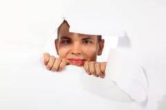 Homem novo que olha para fora no furo no papel imagens de stock