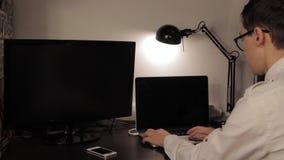 Homem novo que olha pensativo e que usa o portátil filme