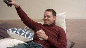 Homem novo que olha a tevê na cama e que bebe o chá Fotografia de Stock