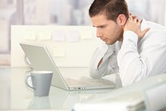Homem novo que olha tired no escritório Fotografia de Stock Royalty Free