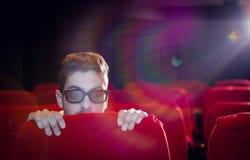 Homem novo que olha um filme 3d assustador Fotografia de Stock Royalty Free