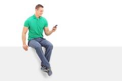Homem novo que olha um telefone celular assentado no painel Imagens de Stock Royalty Free