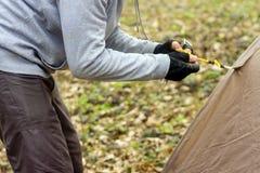Homem novo que põe uma barraca nas madeiras a Imagem de Stock