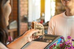 Homem novo que paga o dinheiro no contador do registro foto de stock royalty free