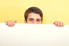 Homem novo que peeping ou que olha sobre uma placa branca Fotografia de Stock